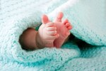 two-cute-tiny-baby-feet-wrapped-in-a-blue-green-aqua-knitted-blanket